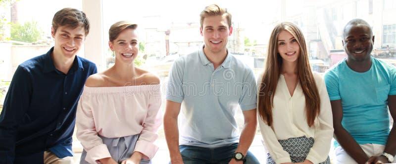 看与微笑的青年人照相机,当坐在办公室时 图库摄影