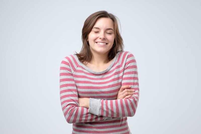 看与快乐和迷人的微笑的年轻女人照相机 免版税库存图片