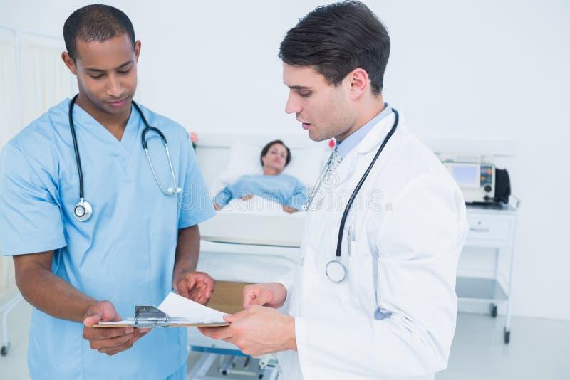 看与患者的医生报告在医院 免版税库存照片