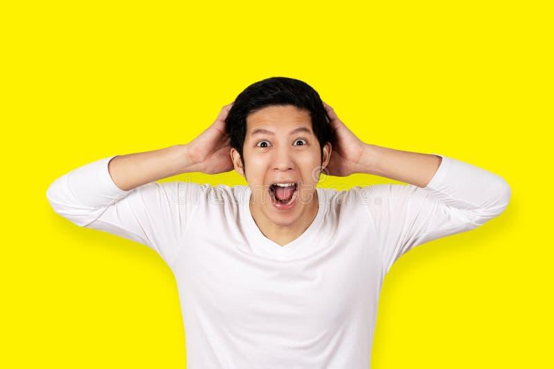 看与感觉惊奇,激动的或者震惊面孔的偶然白色衬衣的年轻可爱的亚裔人照相机 免版税库存照片