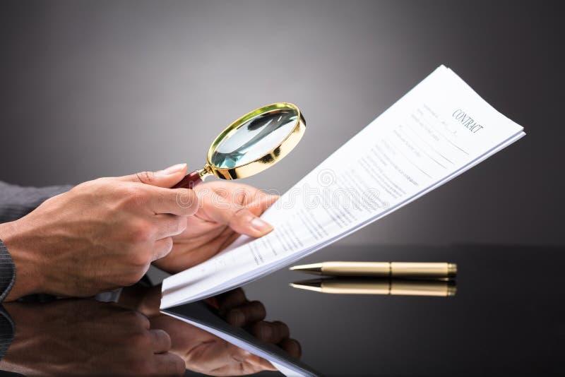 看与放大镜的法官文件 免版税库存照片
