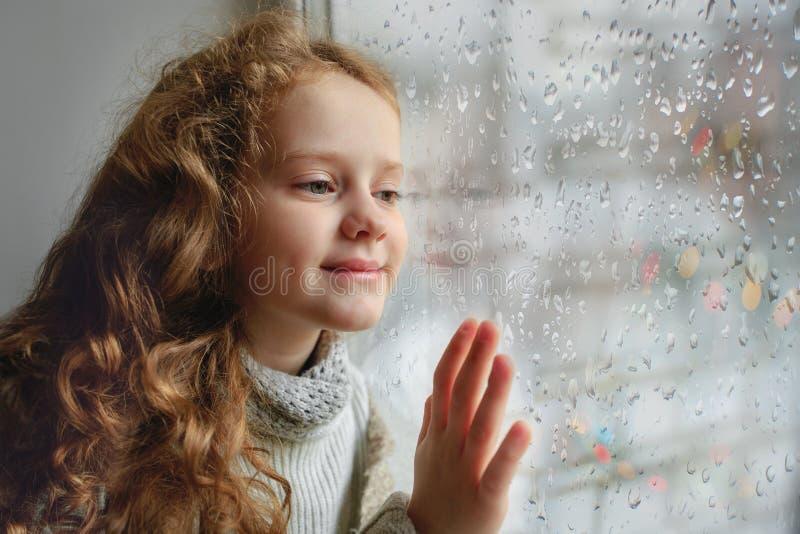 看与湿玻璃秋天坏wea的愉快的孩子窗口 免版税图库摄影