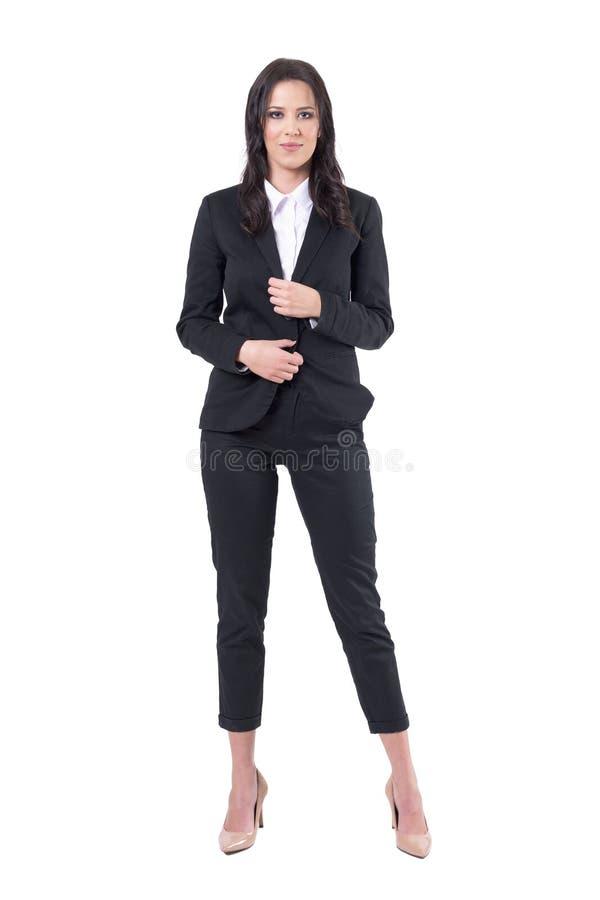 看与确信的微笑的黑衣服的迷人的微笑的女商人照相机 图库摄影