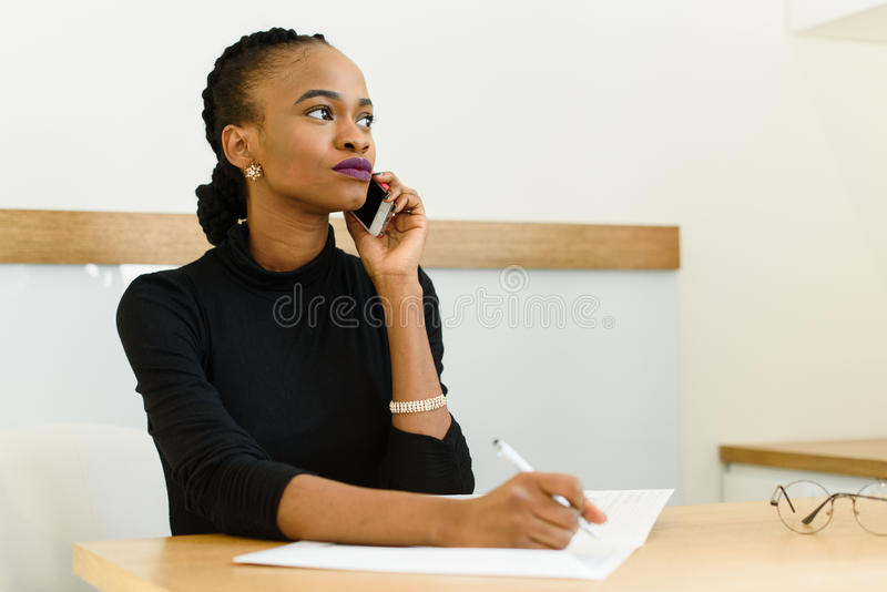 看与笔记薄的电话的严肃的确信的年轻非洲或黑人美国女商人在办公室 库存照片