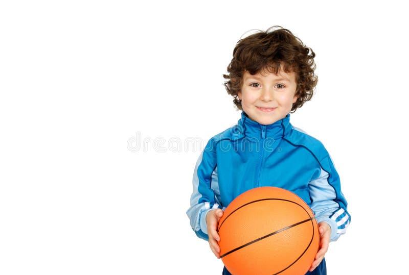 看与篮子球的微笑的男孩照相机 免版税库存图片