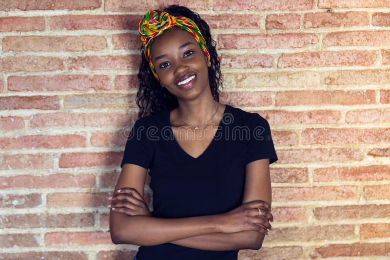 看与胳膊的愉快的年轻女人照相机横渡,当站立在墙壁前面时 库存照片