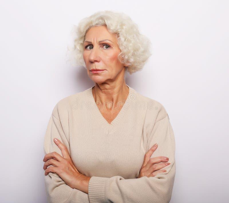 看与胳膊的确信的年长妇女画象照相机横渡在胸口 免版税库存图片