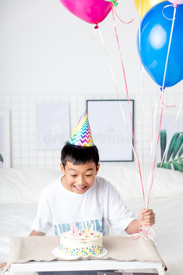 看与蜡烛的激动的亚裔男孩蛋糕,生日快乐生日聚会 免版税库存图片