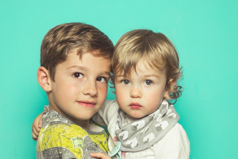 看与轻微的微笑的一个小男孩和一个小女孩的画象照相机 免版税图库摄影