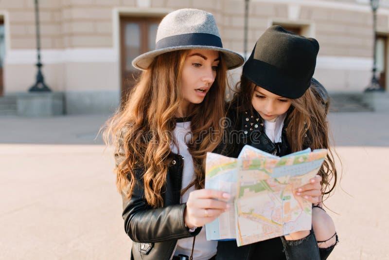 看与迷茫的面孔表示的华美的长发妇女地图 戴黑帽会议的女孩画象 库存图片