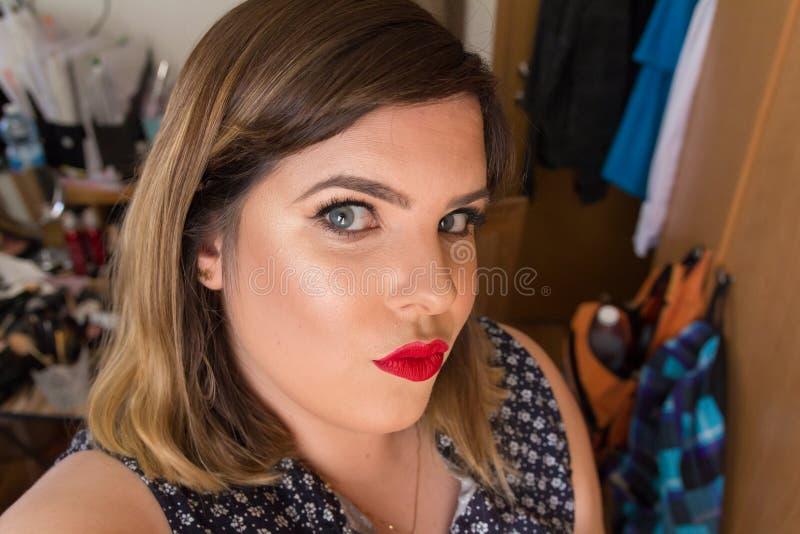 看与鸭子面孔姿势的美丽的性感的少妇照相机 免版税库存照片