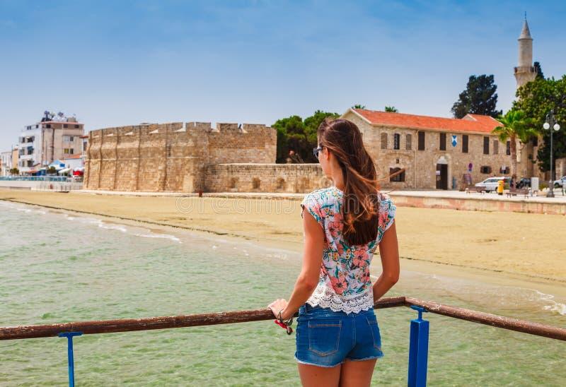 看中世纪城堡的年轻旅游妇女在拉纳卡,塞浦路斯 免版税库存照片