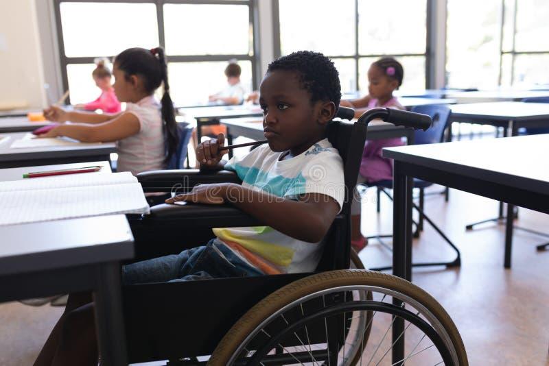 看书桌的体贴的功能失效男小学生在教室 库存照片