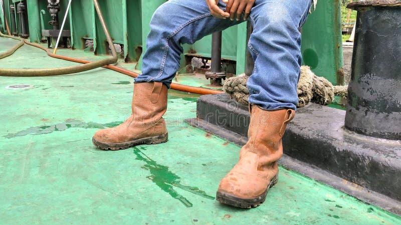 看了坐工作者的鞋子和牛仔裤 图库摄影