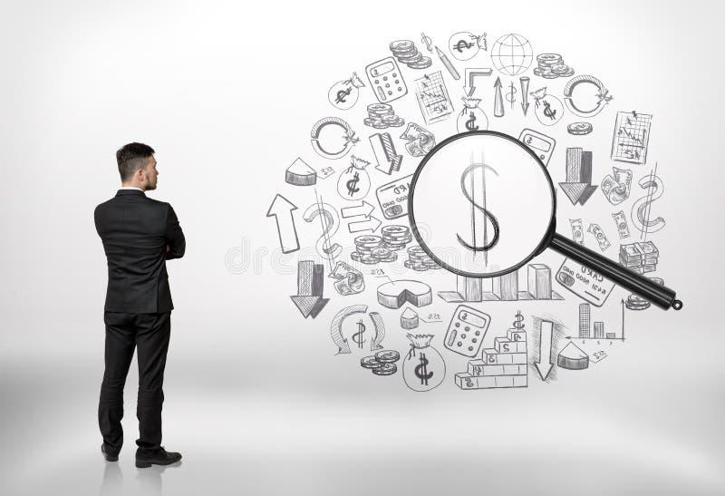 看事务的商人通过放大器和看美元的符号乱画 免版税库存图片