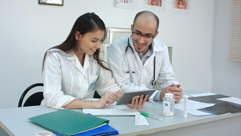 看事的两名医护人员滑稽在片剂和笑 图库摄影
