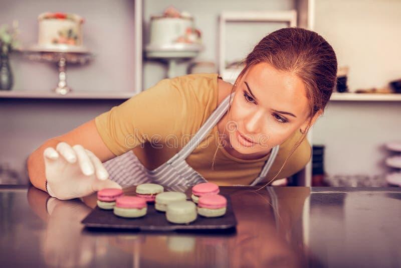看五颜六色的法式蛋糕铺的被集中的年轻女人 免版税图库摄影