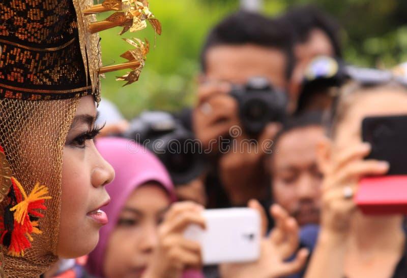 看人群的传统Minang舞蹈家旁边画象  库存图片