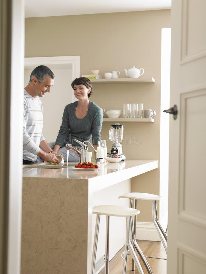 看人洗涤的器物的妇女在厨房里 库存图片