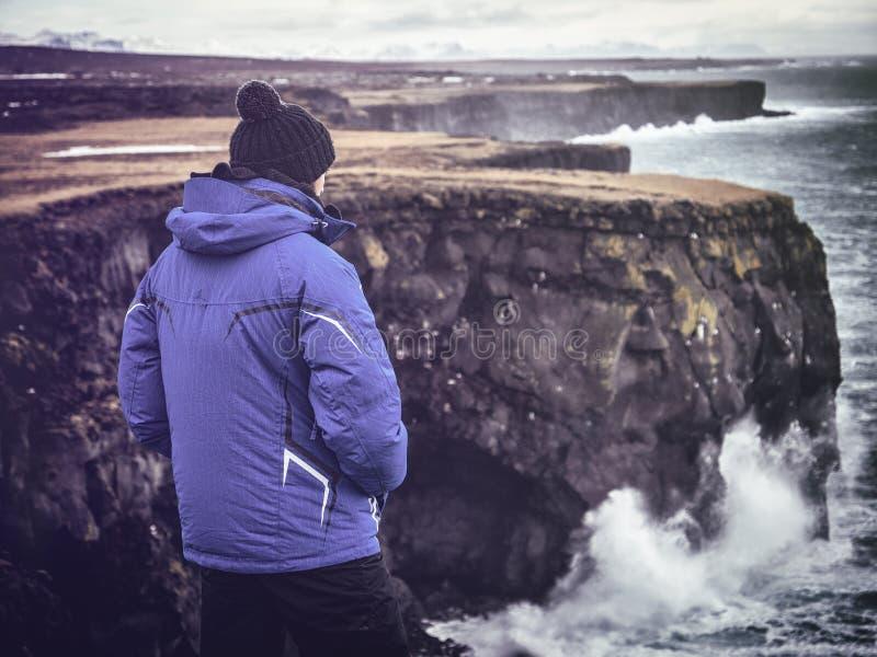看从峭壁的男性旅客风雨如磐的海 库存图片