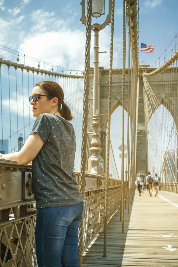 看从布鲁克林大桥的妇女都市风景在纽约 库存图片