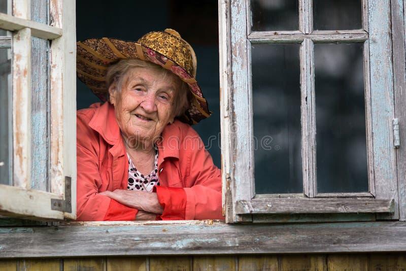 看从窗口的草帽的一名年长妇女 图库摄影