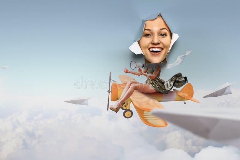 看从被撕毁的纸孔和乘坐玩具飞机拼贴画的妇女 库存图片