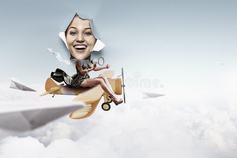 看从被撕毁的纸孔和乘坐玩具飞机拼贴画的妇女 库存照片