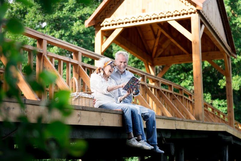 看他们的家庭照片册页的退休的已婚夫妇 免版税图库摄影