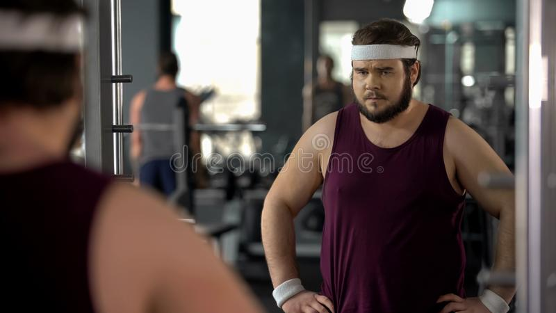 看他的在健身房、饮食和体育的不快乐的超重人镜象反射 免版税图库摄影