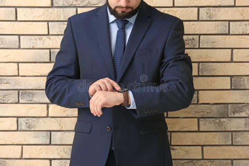 看他的在砖背景的人手表 E 库存图片
