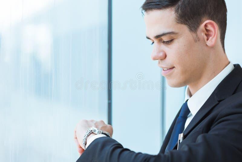 看他的手表的英俊的商人 图库摄影