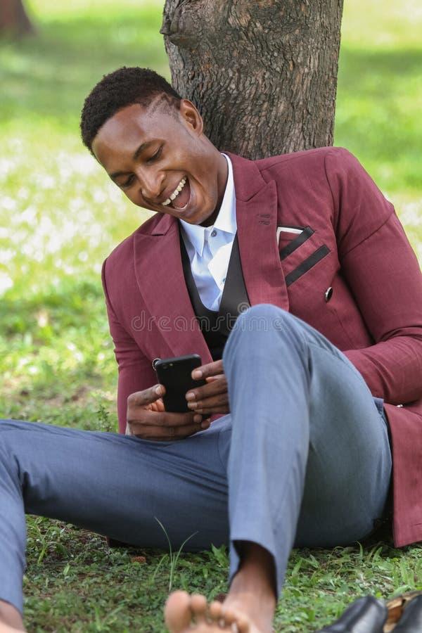 看他的电话的一名愉快的男性黑人工作者 库存照片