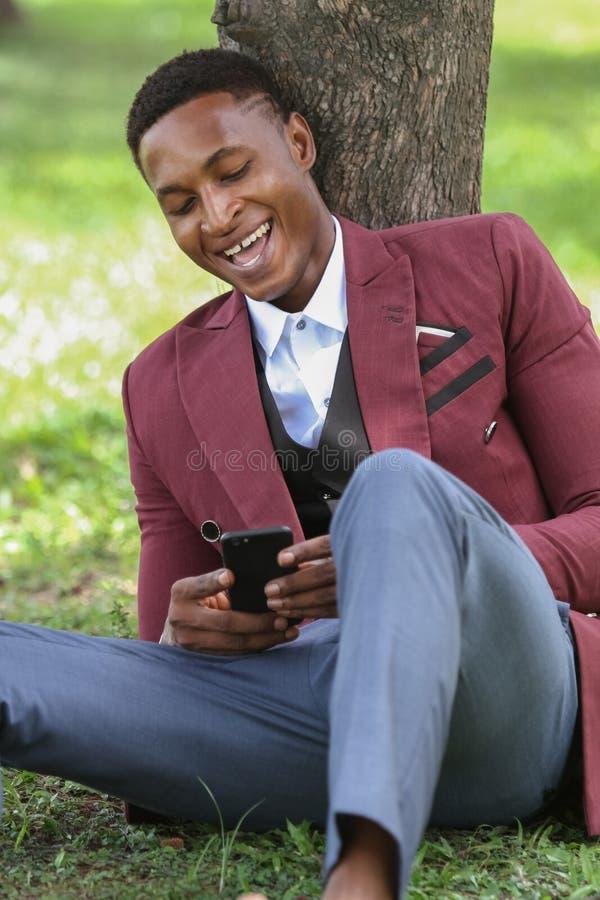 看他的电话的一名愉快的男性黑人工作者 免版税库存图片