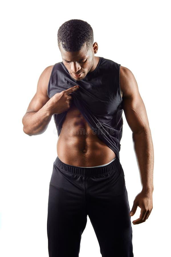 看他的胃的年轻肌肉运动员 免版税库存图片