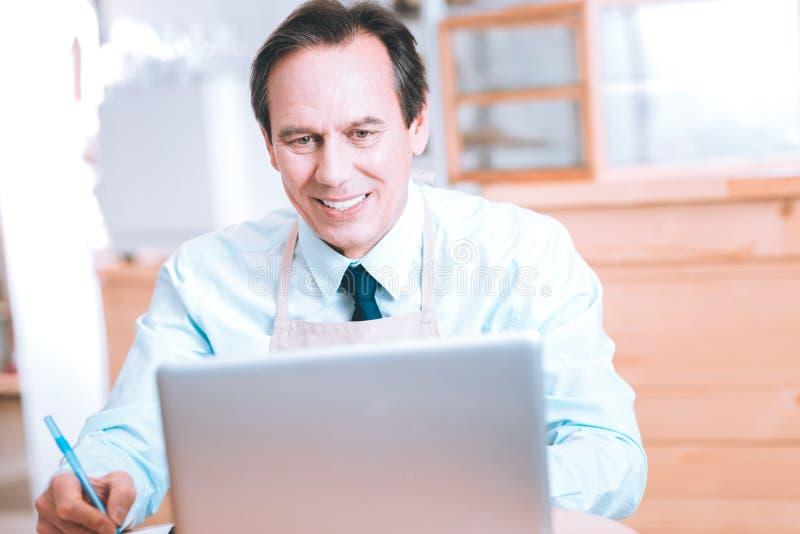 看他的计算机的屏幕高兴男性收养 免版税图库摄影