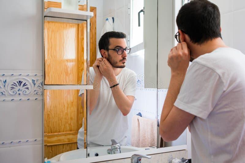 看他自己的人在一个镜子在卫生间里 他得到耳环 免版税库存图片