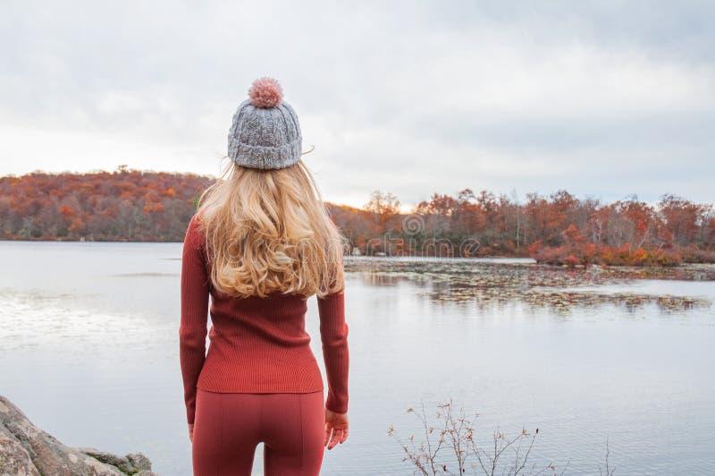 看令人惊讶的湖和森林,旅行癖旅行概念的温暖的帽子和秋天衣裳的妇女旅客 库存照片