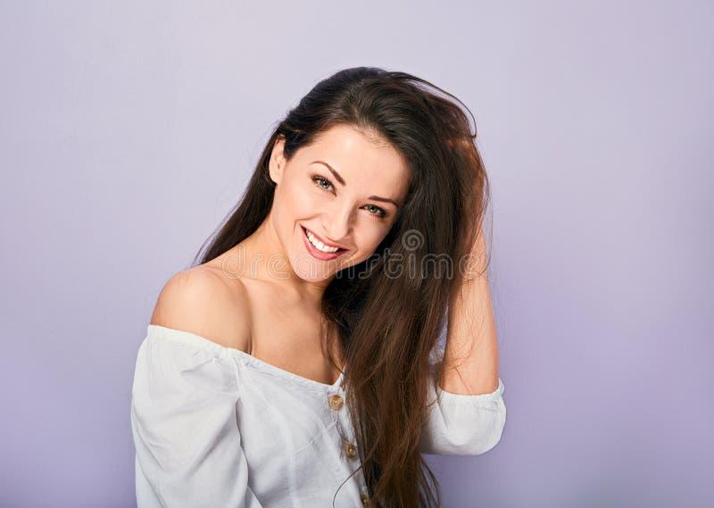 看以愉快的美丽的自然暴牙的微笑的妇女在有长的卷曲发型的白色衬衫 r 免版税库存照片