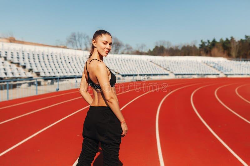 看伟大好和的感受 看见从在体育样式的后面健康妇女慢跑者在体育场穿衣在早晨赛跑 库存图片