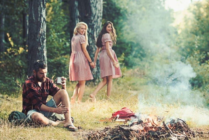 看体贴的人的两个愉快的微笑的女孩坐草 有胡子的人伐木工人衬衣想法的一会儿 库存照片