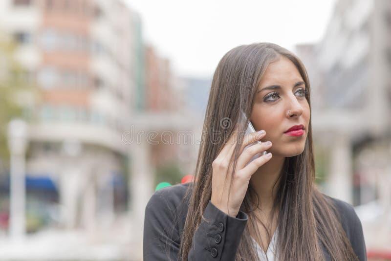 看体贴的女商人谈话由电话和  免版税库存图片