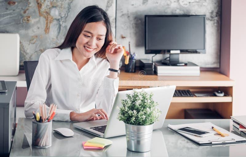 看便携式计算机和微笑的面孔a的亚洲女实业家 免版税库存图片