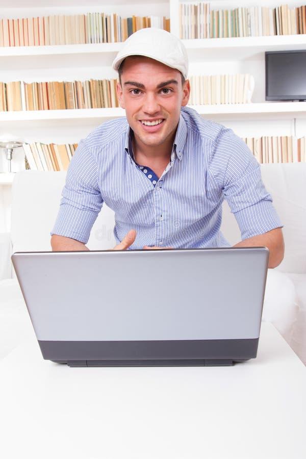 看便携式计算机屏幕微笑的年轻商人 库存图片