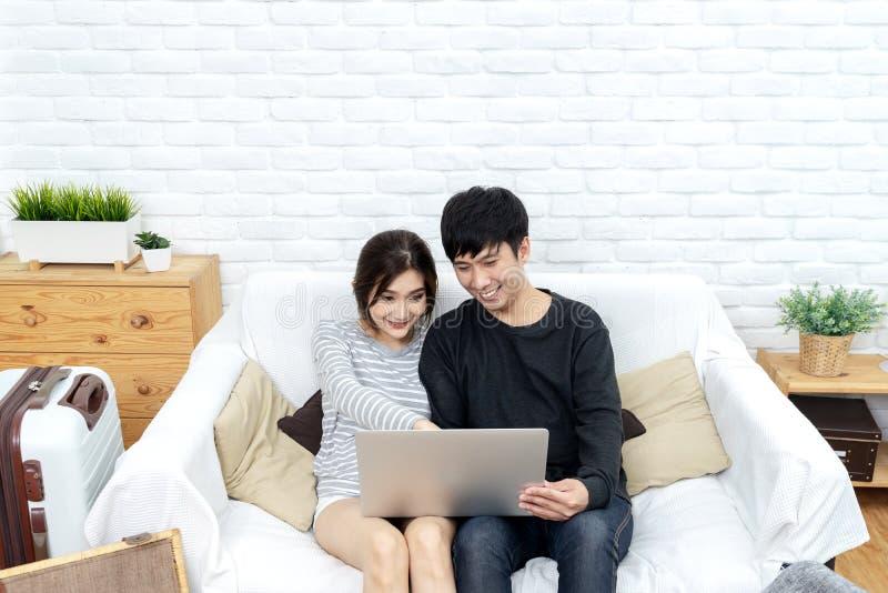 看便携式计算机的年轻亚洲夫妇搜寻旅行计划、书旅馆客房、购买票或者购买旅行保险 免版税库存图片