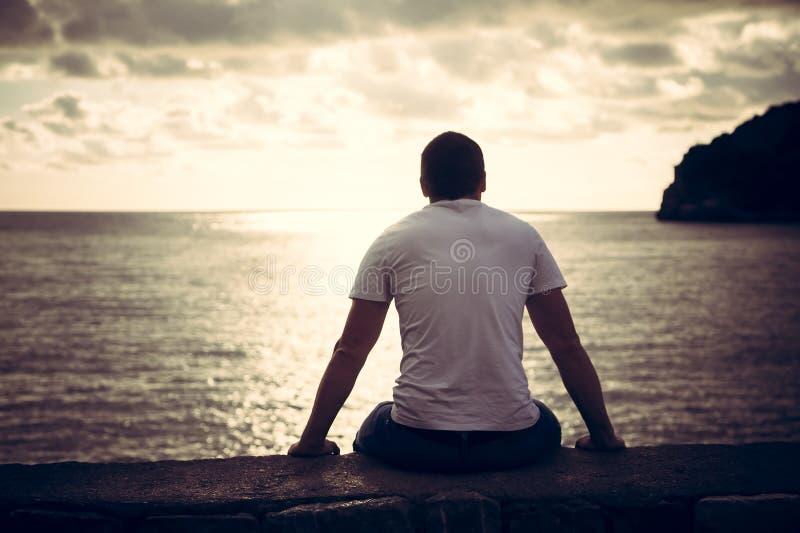 看充满希望的孤独的人与阳光的天际在与光的作用的日落期间在隧道尽头 免版税图库摄影