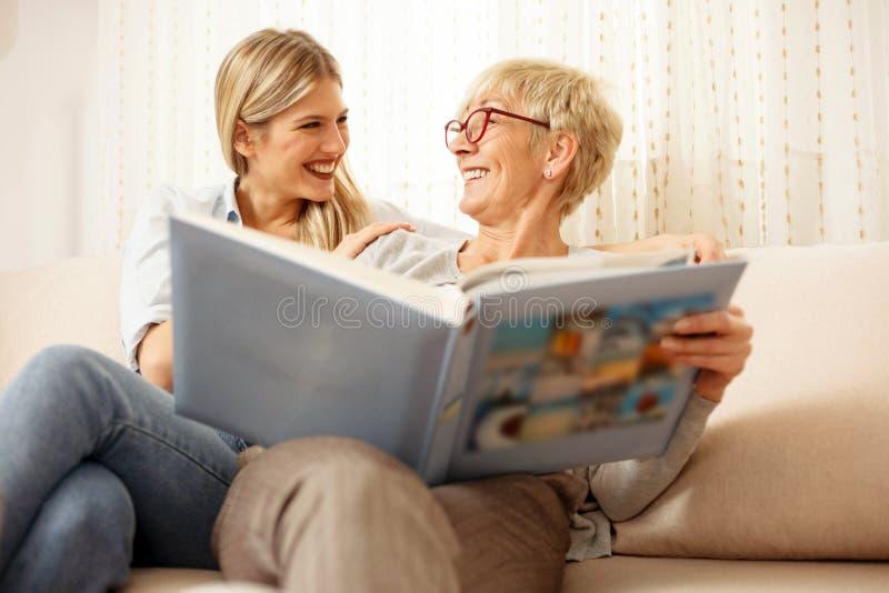 看全家福象册的母亲和女儿 免版税库存图片