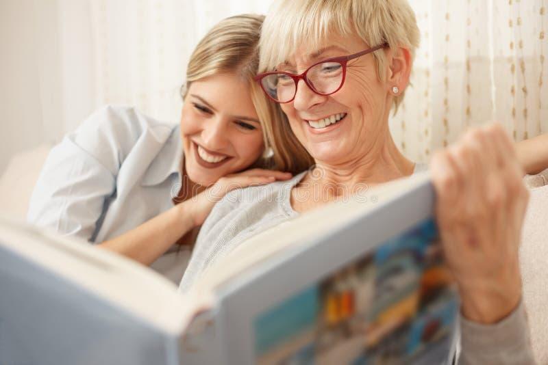 看全家福象册的母亲和女儿 免版税图库摄影