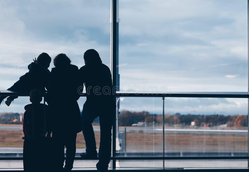 看全景和等待在机场的家庭小组的剪影 免版税库存图片