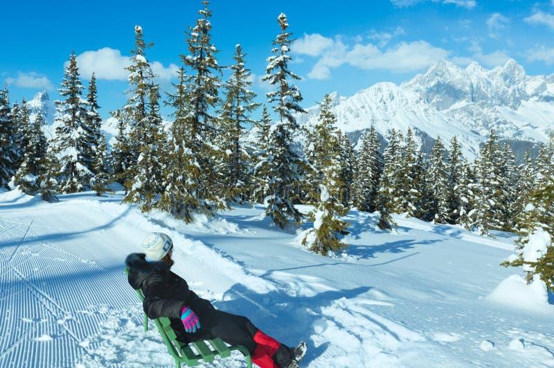 看冬天山的长凳的妇女。 免版税库存图片